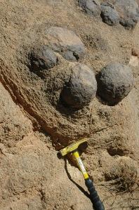 En gang var dette en stor stein, som delte seg opp og ble til fire små. Nå har de blitt helt runde. Geologhammeren viser at det er et skikkelig geologibilde, og om man vet hvor stor en sånn hammer er forstår man med en gang hvor store steinene er.